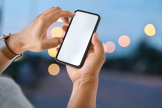 Mâle main tenant un écran mobile mobile smartphone dans la nuit de la rue. Photo Premium