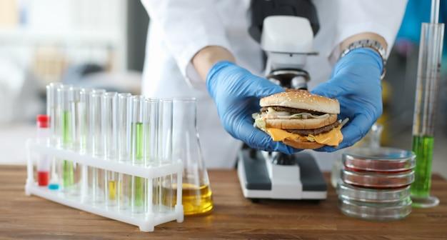 Mâle Main Tenir Burger à La Main Avec Des Gants De Protection Bleus Photo Premium