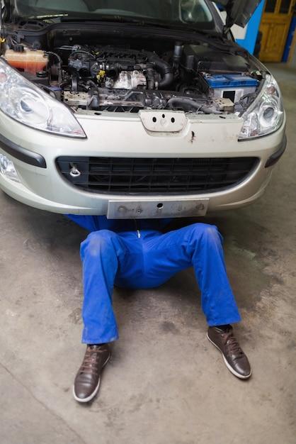 Mâle mécanicien couché sous voiture Photo Premium