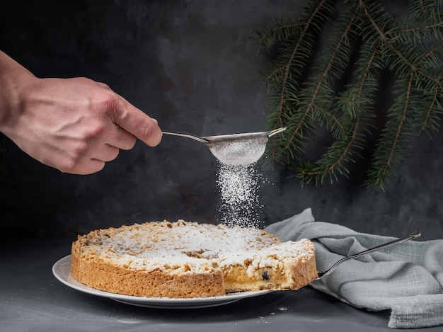 Un Mâle Saupoudre De Sucre En Poudre Sur Une Tarte Aux Pommes, Debout Sur Une Table. Photo Premium