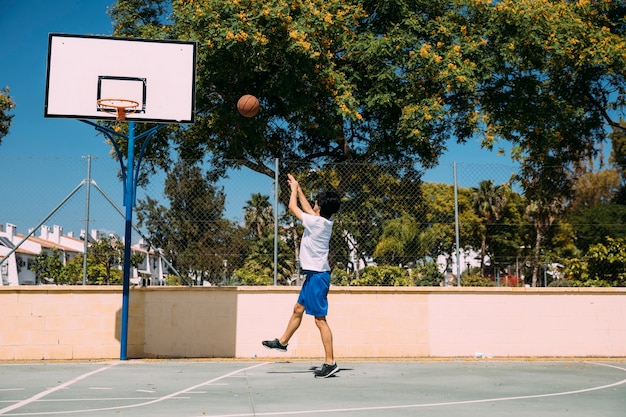 Mâle sportif lancer la balle dans le cerceau sur fond urbain Photo gratuit