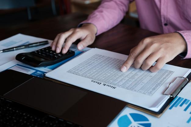 Mâle utilisant une calculatrice et un ordinateur portable pour analyser le marché boursier Photo Premium