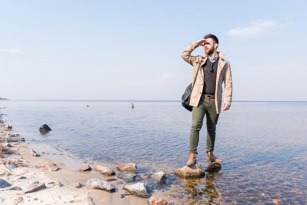 Mâle voyageur debout près du lac protégeant ses yeux Photo gratuit