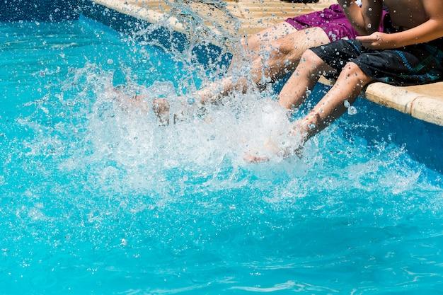 Les mâles parmi les éclaboussures d'eau au bord de la piscine Photo gratuit