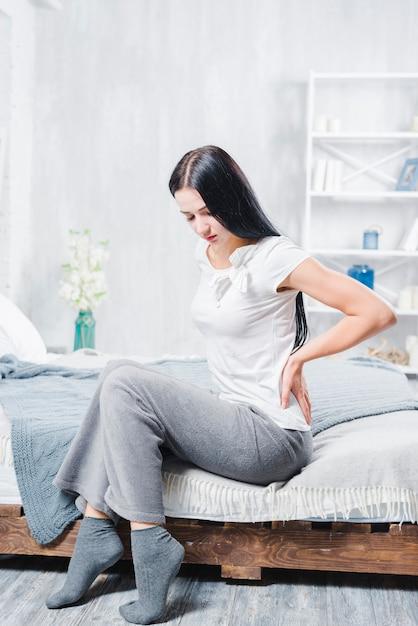Malheureuse femme assise sur un lit en bois souffrant de douleurs au dos Photo gratuit