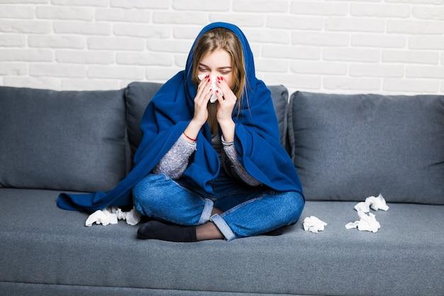 Malheureuse Femme Fatiguée Bouleversée Est Assise Sur Un Canapé à La Maison Souffrant D'un Rhume Et à L'aide De Serviettes, Avoir Froid Photo gratuit