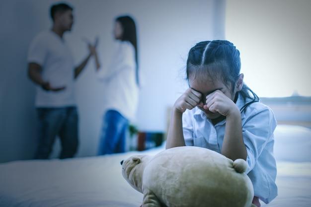 La malheureuse fille assise près des parents qui discutent sur le lit Photo Premium