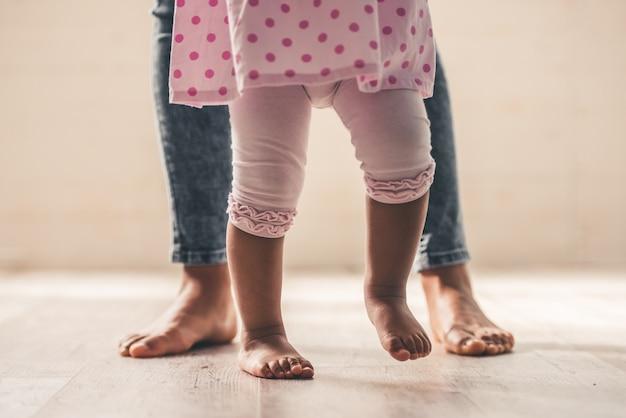Maman afro-américaine et les jambes de son bébé mignon. Photo Premium