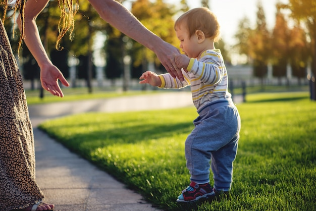 Maman aide un bébé mignon à marcher sur une pelouse verte dans la nature par une journée d'automne ensoleillée Photo Premium