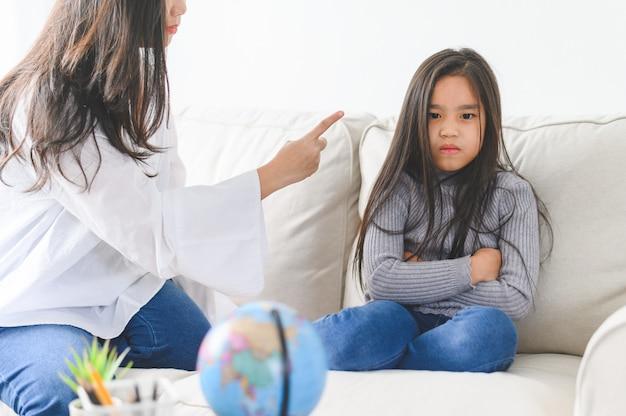 Maman asiatique en colère assise avec sa petite fille, maman gronde pour la discipline comportement mauvais gamin capricieux. Photo Premium
