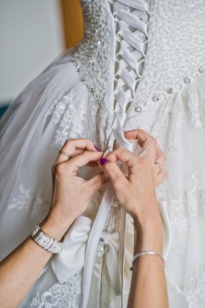 Maman attachant la robe de mariée de la mariée, l'intérieur de l'hôtel Photo Premium