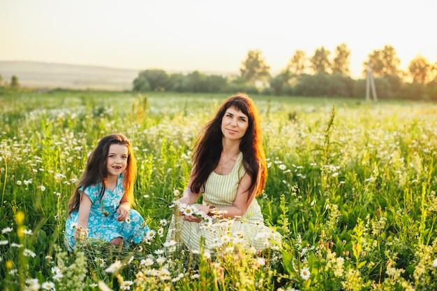 Maman avec bébé dans un champ de marguerites au coucher du soleil. tonifiant Photo Premium
