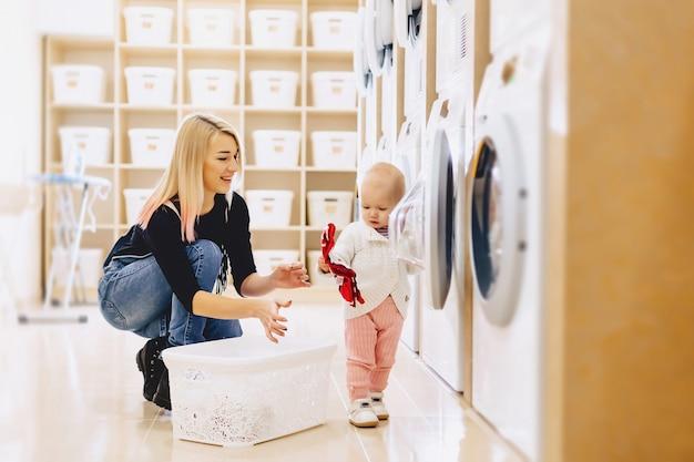Maman et bébé dans la lessive prennent des choses et jouent Photo Premium