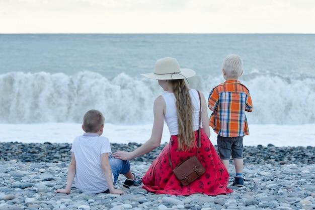 Maman Et Deux Fils Assis Sur La Plage Et Regardant Les Vagues. Vue Arrière Photo Premium