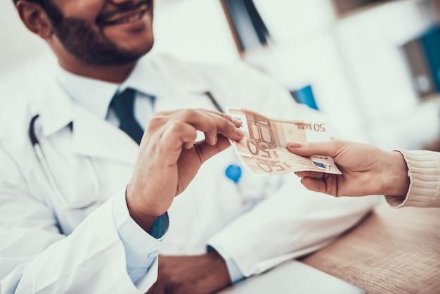 Maman donne de l'argent à un médecin indien. le docteur prend de l'argent Photo Premium