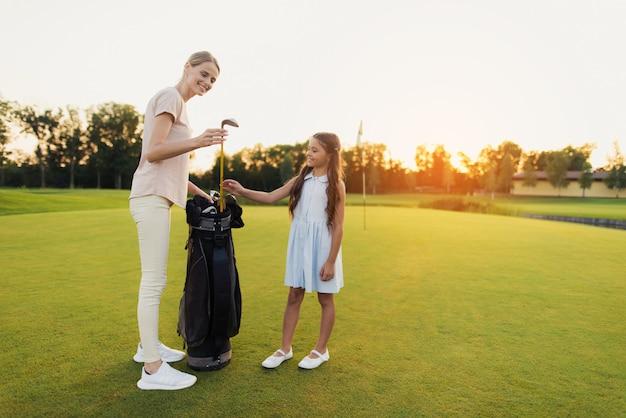 Maman emmène un club apprendre aux enfants à jouer au golf en famille. Photo Premium