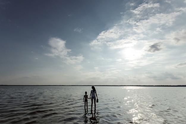 Maman et l'enfant se tiennent dans l'eau contre le magnifique coucher de soleil sur le lac Photo Premium