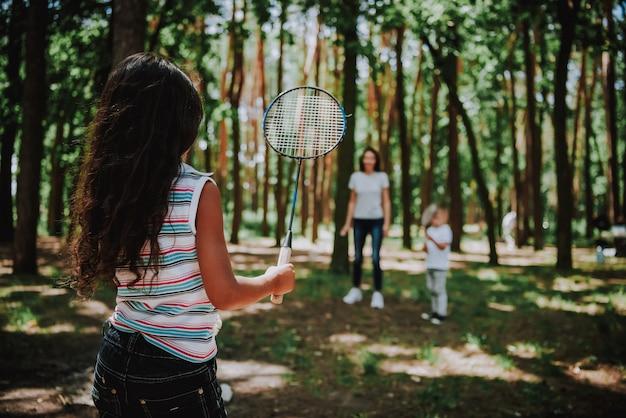 Maman avec des enfants jouant au badminton à sunny park Photo Premium