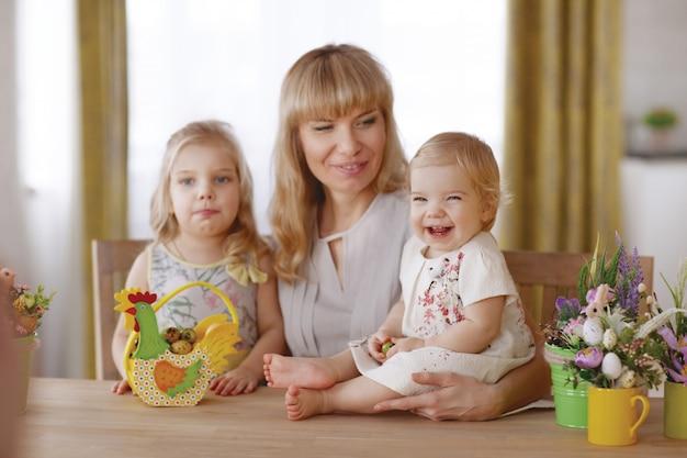 Maman et enfants avec des oeufs de pâques colorés à la table du dîner Photo Premium
