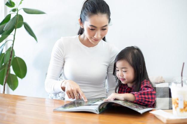 Maman enseigne à sa fille à lire un livre. Photo Premium