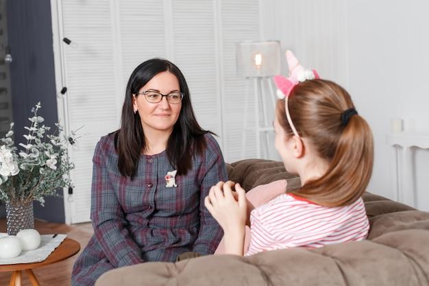 Maman Et Fille Assise Sur Le Canapé Et Bavardant. Adolescente Avec émotions Raconte L'histoire De Sa Mère Photo Premium