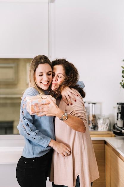 Maman et fille avec cadeau embrassant dans la cuisine Photo gratuit