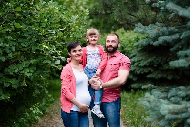 Une maman, une fille et un papa enceintes se promènent dans le parc. Photo Premium
