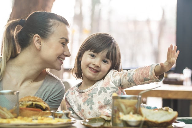 Maman Avec Une Jolie Fille Mangeant De La Restauration Rapide Dans Un Café Photo Premium