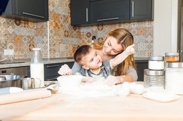 Maman Joue Avec Enfant Dans La Cuisine. La Cuisine Est Faite Est De Couleurs Sombres Et De Style Roustique. Photo gratuit