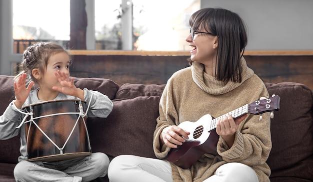 Maman Joue Avec Sa Fille à La Maison. Leçons Sur Un Instrument De Musique. Développement Des Enfants Et Valeurs Familiales. Le Concept De L'amitié Et De La Famille Des Enfants. Photo gratuit