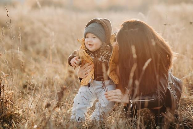 Maman joue avec son petit bébé garçon, famille heureuse à pied Photo Premium