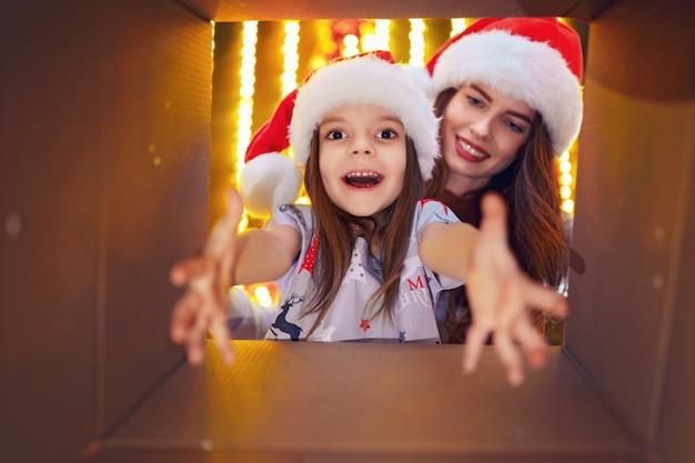 Maman Joyeuse Et Sa Fille Mignonne Ouvrant Un Cadeau De Noël Photo Premium