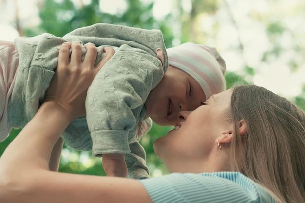 Maman marche avec le bébé dans le parc. le bébé dans ses bras. printemps. Photo Premium