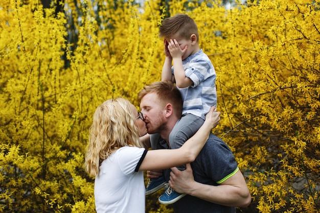 Maman et papa s'embrassent pendant que leur petit fils ferme les yeux Photo gratuit