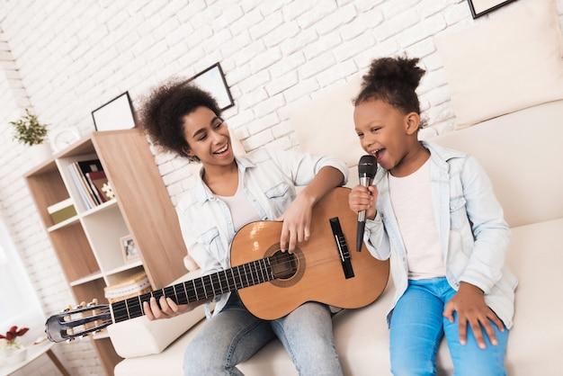 Maman et petite fille chantent ensemble et jouent de la guitare. Photo Premium