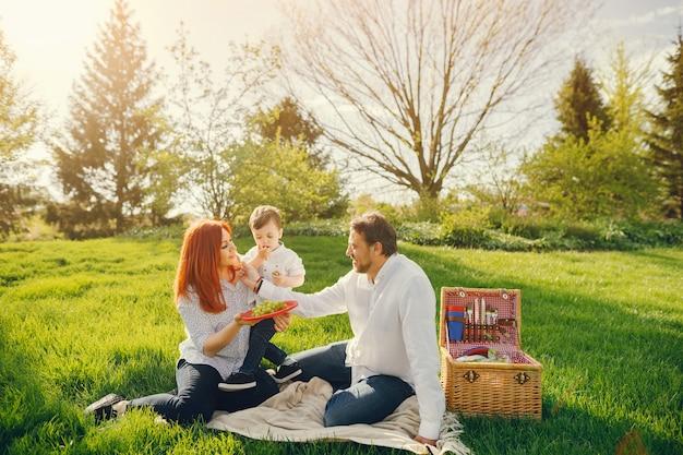 Maman rousse belle et élégante dans un chemisier blanc est assis sur l'herbe avec son bel homme Photo gratuit