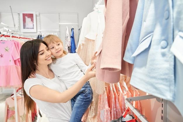 Maman Et Sa Fille Choisissent Des Vêtements Pour Enfants. Photo gratuit