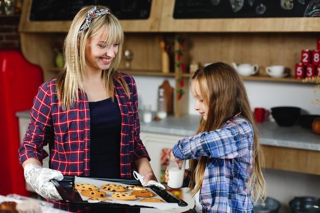 Maman et sa fille dans une cuisine goûtent ensemble des biscuits au chocolat frais et au lait avec du lait Photo gratuit