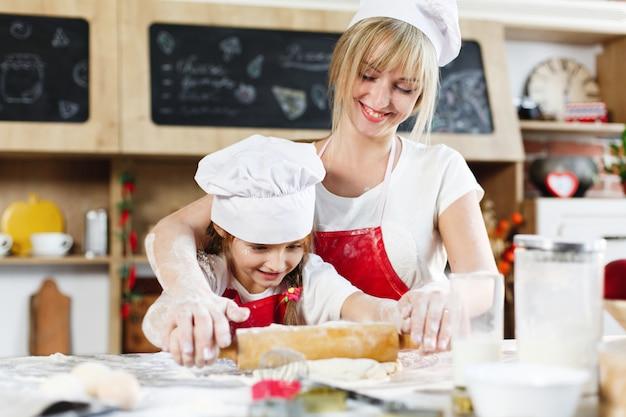 Maman et sa fille dans les mêmes vêtements s'amusent à préparer une pâte dans une cuisine confortable Photo gratuit