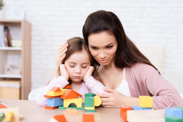 Maman et sa fille jouent avec des cubes en bois. Photo Premium