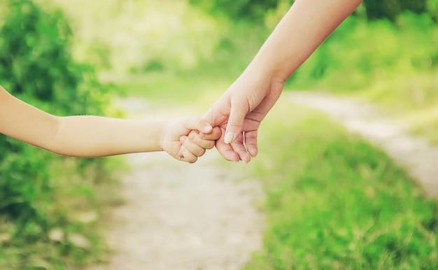 Maman et sa fille marchent le long de la route en se tenant la main. Photo Premium