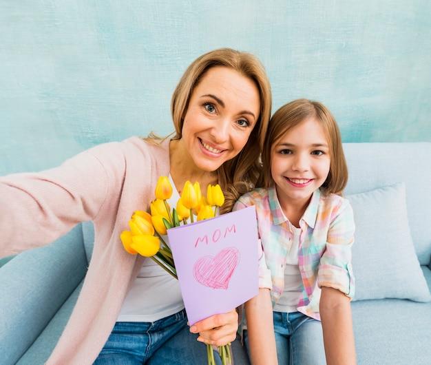 Maman et sa fille avec une photo prise en souriant Photo gratuit