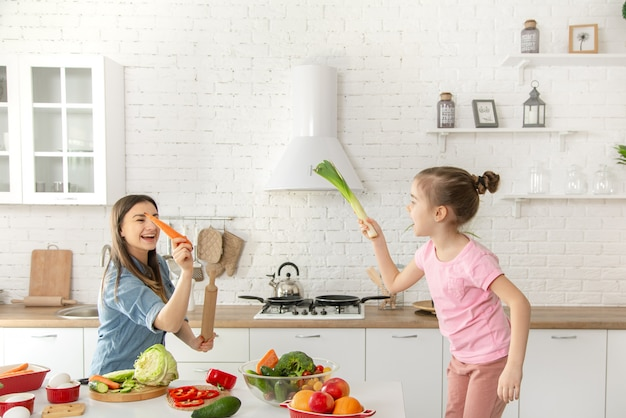 Maman Et Sa Fille Préparent Une Salade Dans La Cuisine. Amusez-vous Et Jouez Avec Les Légumes. Photo gratuit