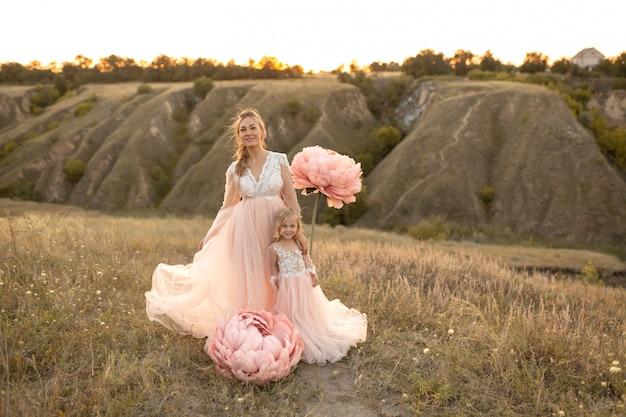Maman avec sa fille en robes de conte de fées roses se promener dans la nature Photo Premium