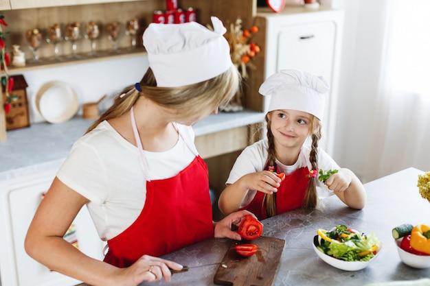 Maman et sa fille s'amusent dans la cuisine en préparant différents légumes pour un dîner Photo gratuit