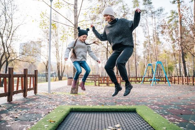 Maman Et Sa Fille Sautant Ensemble Sur Un Trampoline Dans Le Parc En Automne Photo gratuit