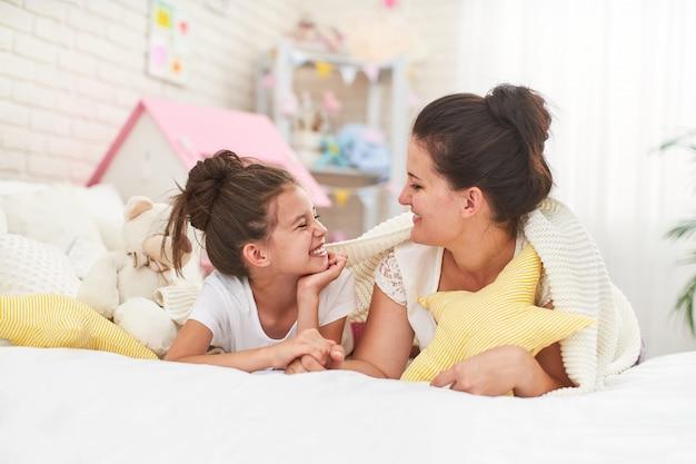 Maman Et Sa Fille Sourire Et Câlin En Position Couchée Sur Le Lit Photo Premium