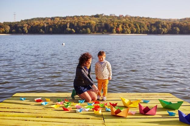 Maman Et Son Fils Jouant Avec Des Bateaux En Papier Au Bord Du Lac Photo gratuit