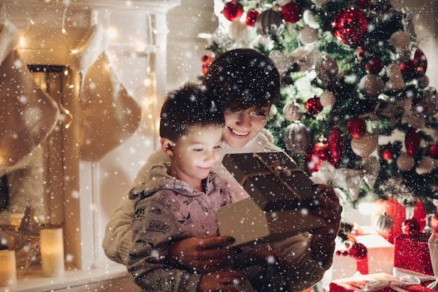 Maman Et Son Fils Ouvrent Un Cadeau De Noël Dans Une Boîte Photo Premium