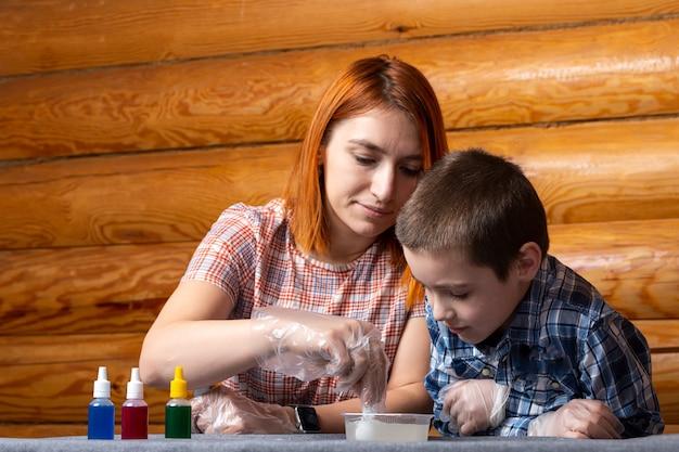 Maman Et Son Fils Remuent Une Cuillère Doseuse Le Mélange Dans Un Récipient Contenant Des éléments Chimiques à La Maison Photo Premium